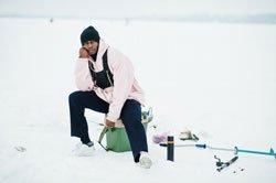 African american fisherman on frozen sea. winter fishing