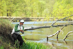 Man fish with spinning on river bank, casting lure. outdoor weekend activity