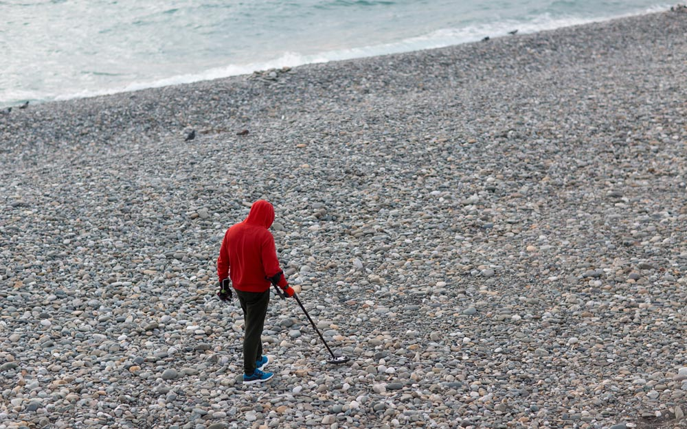 Man with a metal detector is looking for coins and jewelry on the beach
